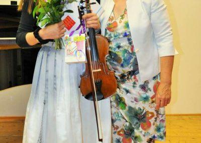 Natáčení absolventů, 24.6.2020, komorní sál ZUŠ Šimáčkova. Děvče s houslemi a velde ní stojící paní učitelka.