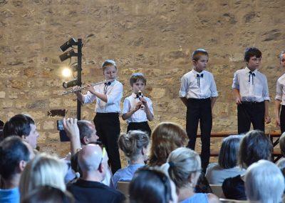 Závěrečný koncert Pueri gaudentes 24.6.2019 - Anežský klášter. Pohled na dva chlapce hrající na flétny a zpívající chlapecký sbor.