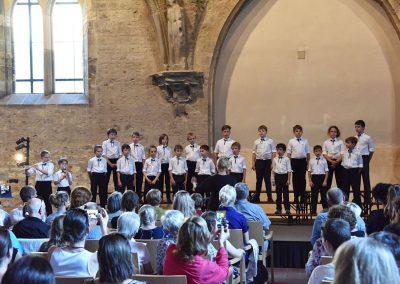 Závěrečný koncert Pueri gaudentes 24.6.2019 - Anežský klášter. Pohled na sbormistryni Z. Součkovou, dva chlapce hrající na flétny a zpívající chlapecký sbor.