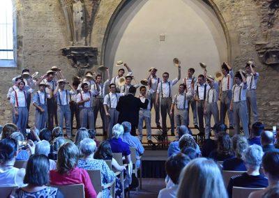 Závěrečný koncert Pueri gaudentes 24.6.2019 - Anežský klášter. Pohled na publikum, pana sbormistra L. Sládka a zpívající mužský sbor.