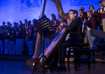 Adventní koncert Pueri gaudentes 9.12.2019 - Betlémská kaple. Pohled na zpívající koncertní sbor a chlapce hrajícího na harfu.