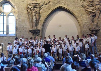 Závěrečný koncert Pueri gaudentes 24.6.2019 - Anežský klášter. Pohled na publikum, pana sbormistra L. Sládka a zpívající koncertní sbor.