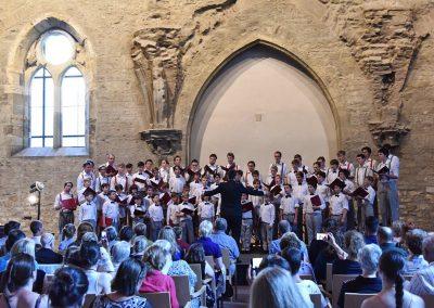 Závěrečný koncert Pueri gaudentes 24.6.2019 - Anežský klášter. Pohled na publikum, pana sbormistra J. Kyjovského a zpívající koncertní sbor.