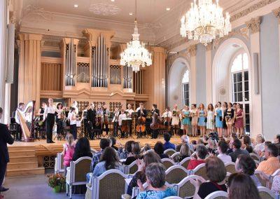Slavnostní koncert ZUŠ Open, HAMU, 31.5.2020. Pohled na orchestr, dirigentku Kristinu Šalšovou a zpívající členky komorního sboru.