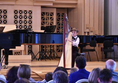 Slavnostní koncert ZUŠ Open, HAMU, 31.5.2020. CHlapec hrající na harfu.