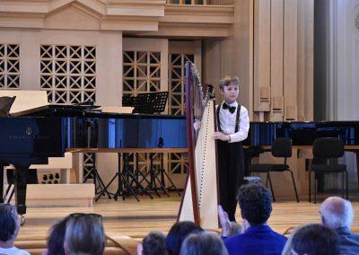 Slavnostní koncert ZUŠ Open, HAMU, 31.5.2020. CHlapec hrající s harfou.