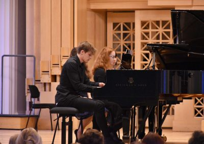 Slavnostní koncert ZUŠ Open, HAMU, 31.5.2020. Klavírní duo pro dva klavíri. Pohled na hrajícího chlapce a děvče.